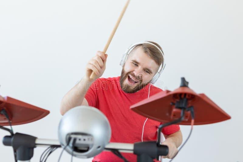 情感、爱好、音乐和人概念-情感鼓手播放电子鼓 免版税库存图片