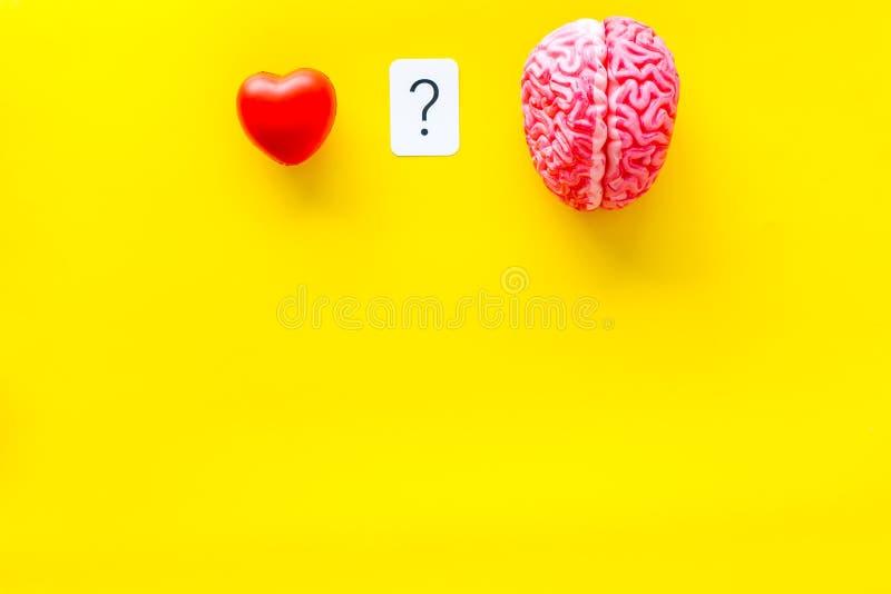 情感和留心概念与脑子和心脏在黄色背景顶视图copyspace 免版税库存图片
