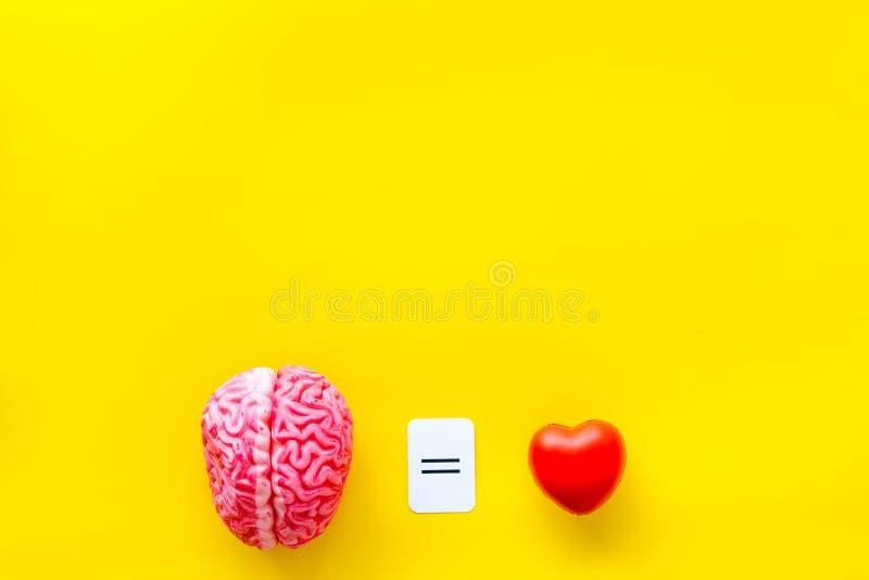 情感和留心概念与脑子和心脏在黄色背景顶视图copyspace 免版税库存照片