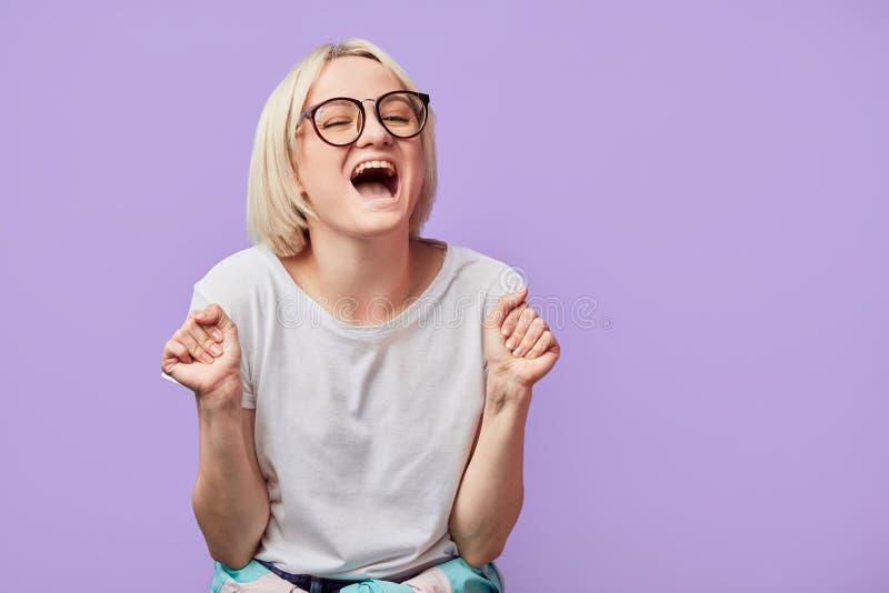 情感妇女在紫罗兰紧握拳头以欢欣,张嘴广泛摆在 免版税库存照片