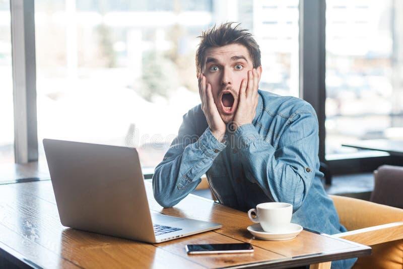 情感害怕的年轻商人画象在蓝色牛仔裤衬衣的在咖啡馆坐,并且尖叫对laptope原因使大 图库摄影