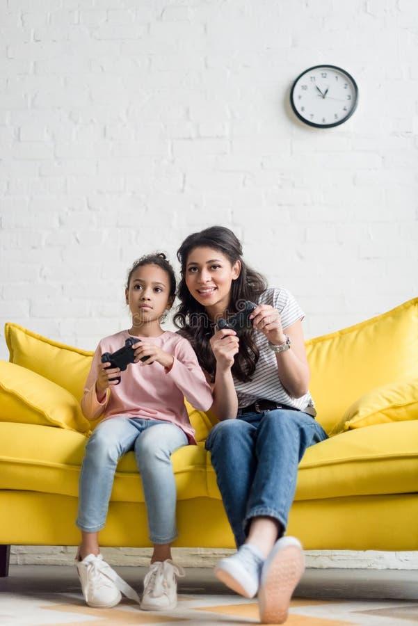情感年轻在家打电子游戏的母亲和女儿 图库摄影