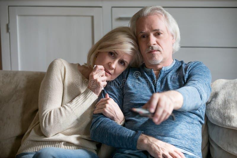 情感年长在电视的夫妇观看的戏曲在家 免版税图库摄影