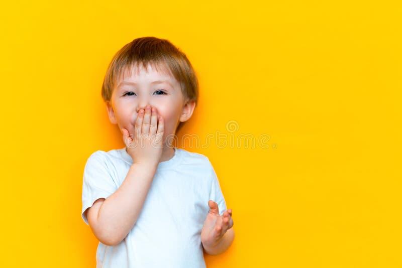 情感惊奇的小男孩覆盖物嘴的关闭用在黄色背景隔绝的手 金发混合的族种亚洲人 库存照片