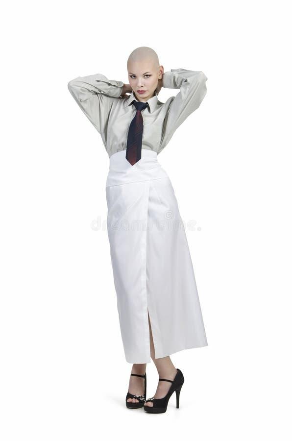 情感画象女孩,被刮的秃头,在有领带和一条白色裙子的一件轻的衬衣 免版税图库摄影