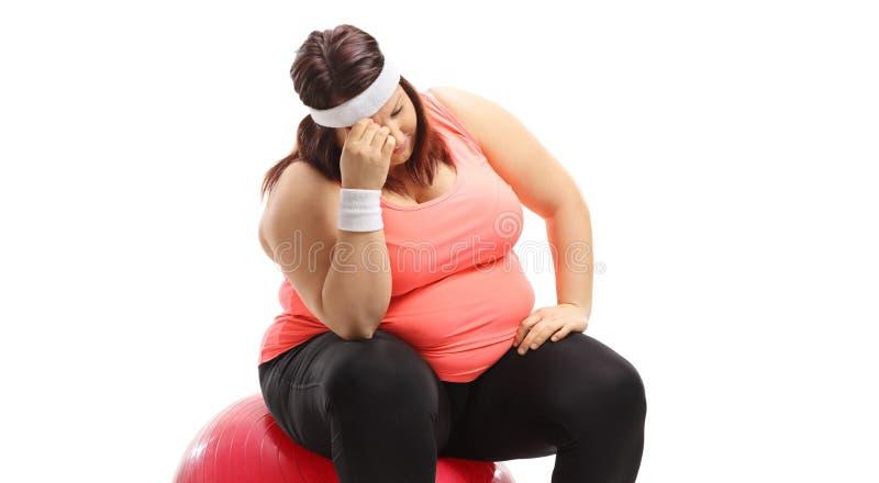 情感超重妇女坐锻炼球 免版税库存照片