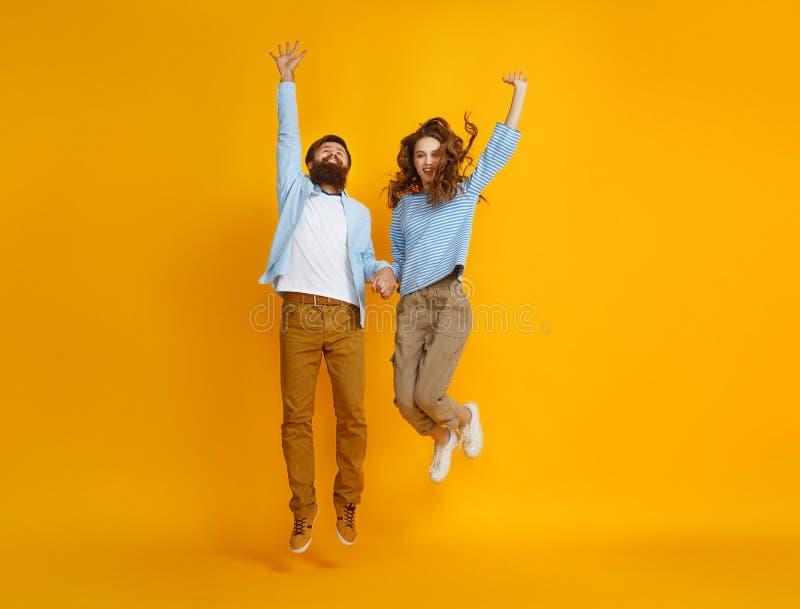 情感跳跃在黄色背景的人男人和妇女夫妇  库存照片