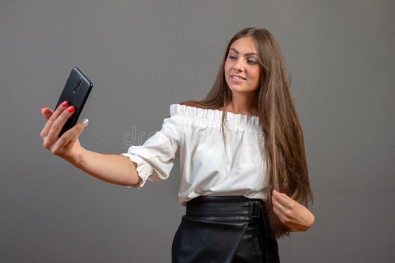 情感逗人喜爱年轻女人摆在被隔绝在谈话灰色墙壁的背景由手机采取selfie -图象 免版税库存图片