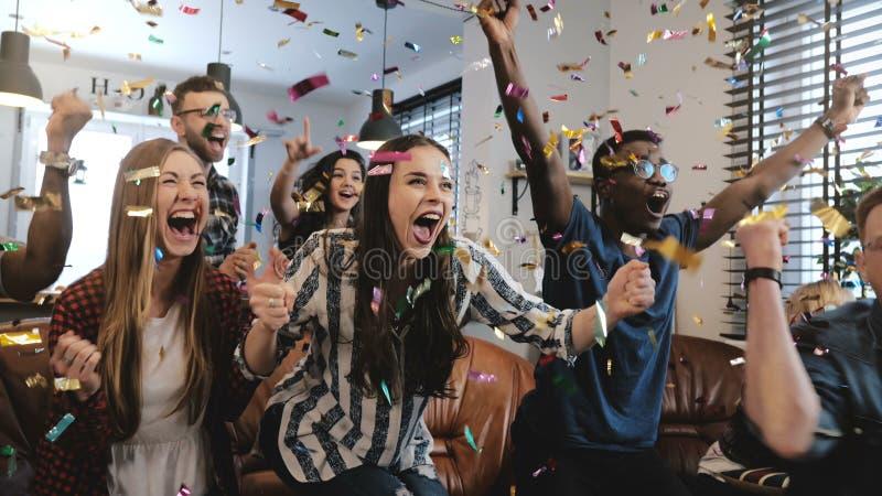 情感 不同种族的爱好者庆祝赢取 五彩纸屑4K慢动作 热情的在电视的支持者呼喊观看的比赛 库存图片