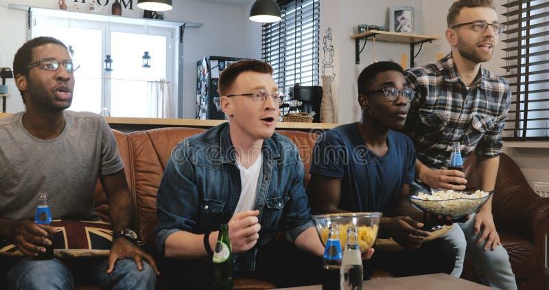 情感 在电视4K讨厌的混合的族种足球迷的非裔美国人的人手表体育庆祝在长沙发的目标用玉米花 库存照片