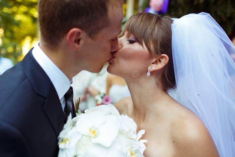 惊人亲吻的婚礼夫妇的特写镜头 库存照片
