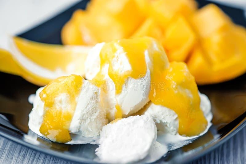 惊人白色冰淇淋用成熟芒果调味汁  特写镜头 免版税库存照片
