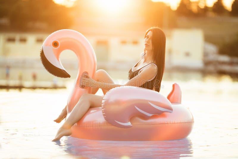 惊人的亭亭玉立的女孩穿黑比基尼泳装在与大海的游泳池坐一个桃红色火鸟床垫 库存照片