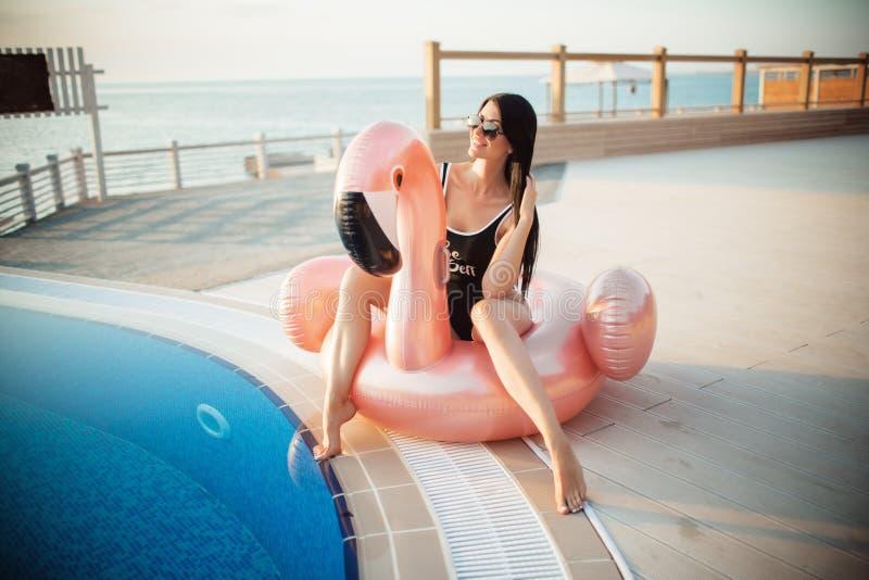 惊人的亭亭玉立的妇女穿黑比基尼泳装在与大海坐一个桃红色火鸟床垫,夏天的游泳池 库存图片