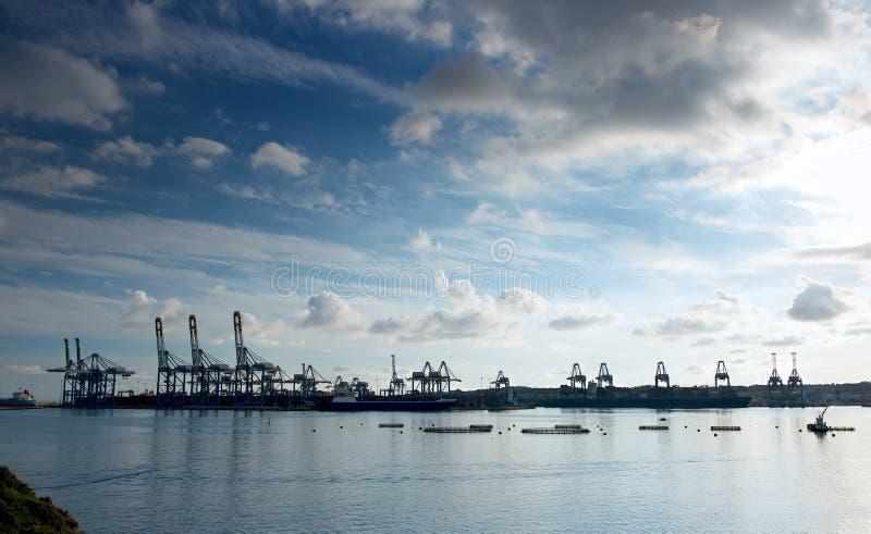 惊人的剧烈的天空、云彩形成和工业货物区黑暗的背景的。货物口岸在Birzebugga,马耳他。 图库摄影