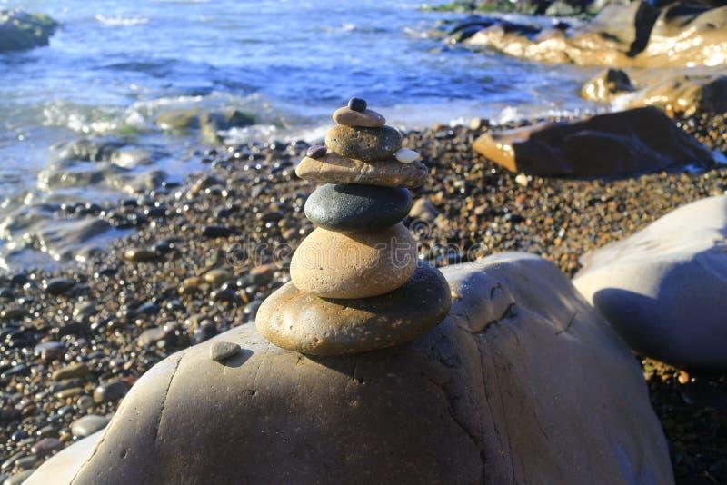 惊人的堆在绿色青苔的石头在海边海岸工作队在大岩石的小卵石平衡 库存照片