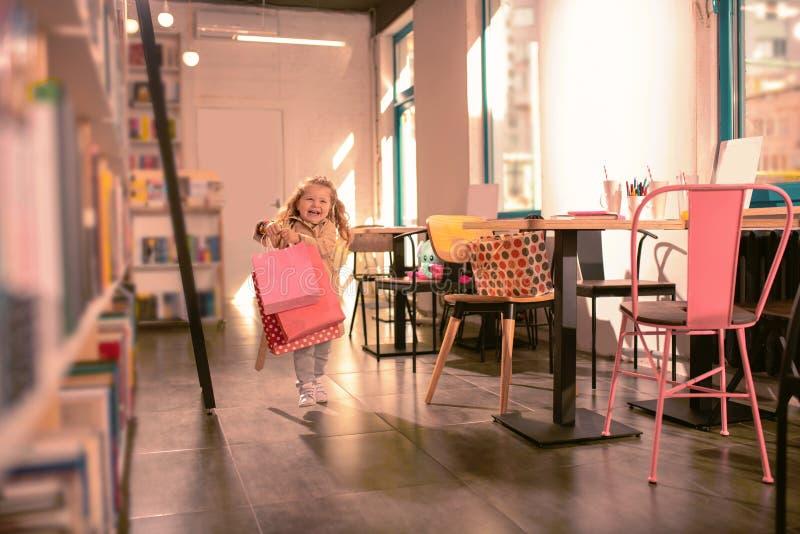 惊人的女婴感觉的幸福,当在咖啡馆时 库存照片