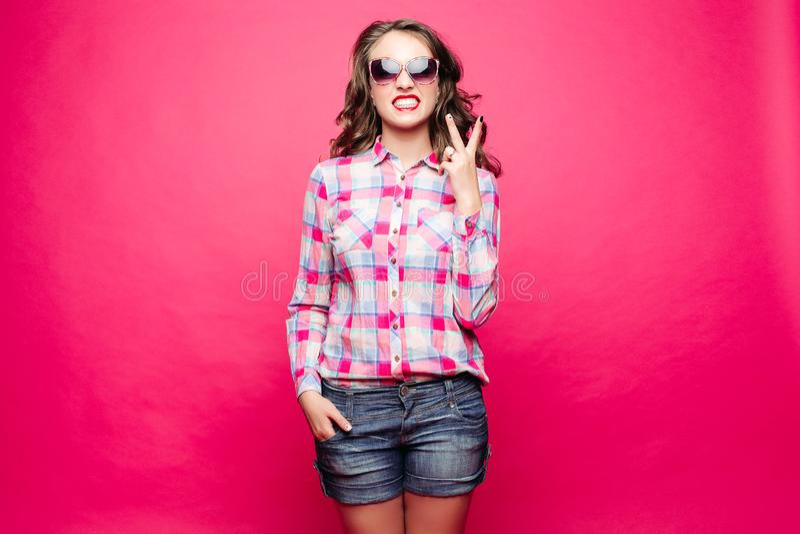 惊人的女孩简而言之显示和平标志的和衬衣佩带的太阳镜 免版税库存照片