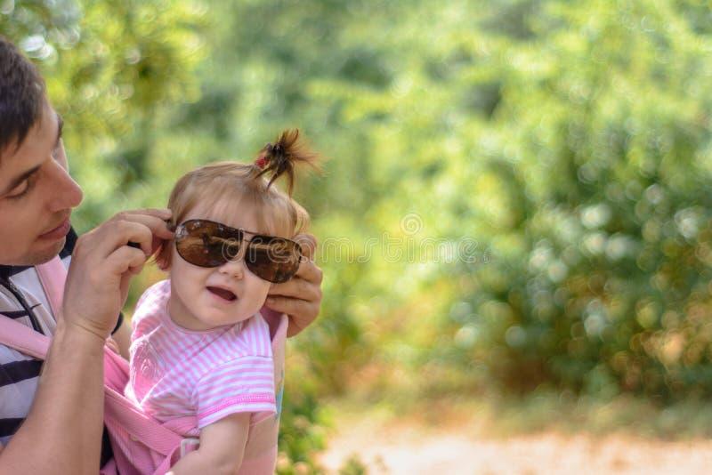 惊人的小女孩使用与有她的父亲的太阳镜 免版税库存图片