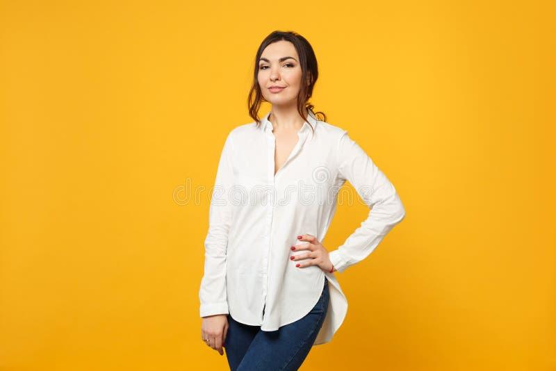 惊人的年轻女人画象白色衬衫的,站立和看照相机的牛仔裤隔绝在橙黄墙壁上 免版税库存照片
