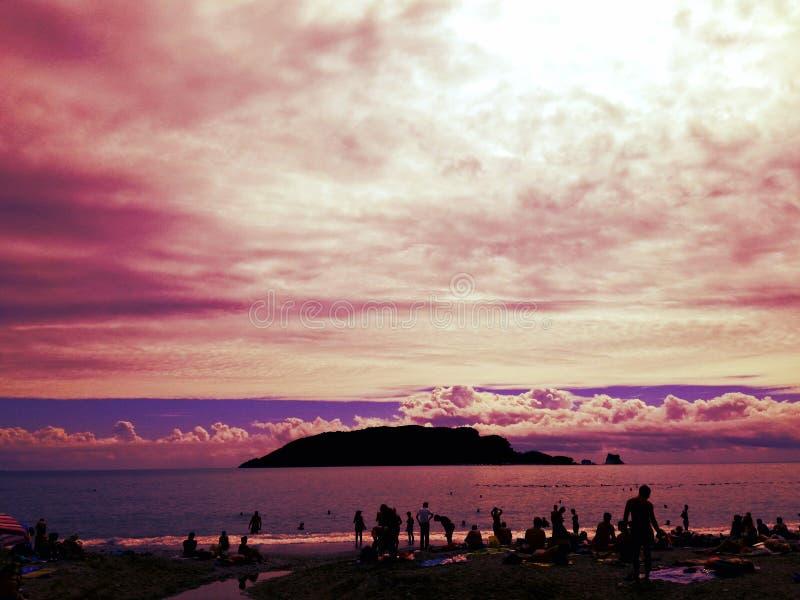 惊人的桃红色日落、完善的天空与云彩,海岛、海和海滩与人 库存图片
