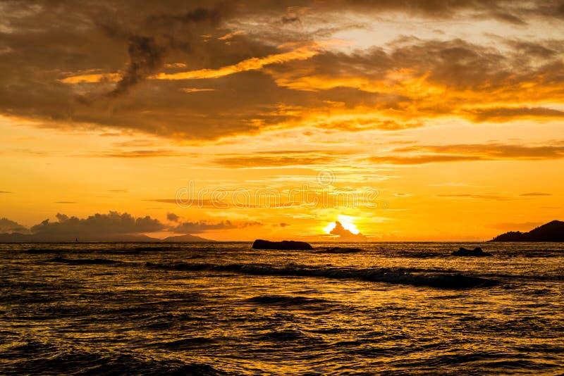 惊人的橙色和多云日落在一个热带海岛, Anse Seve 库存照片