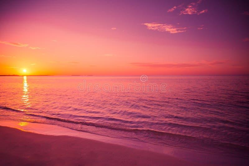 惊人的海滩日落 与软的波浪的松弛颜色 免版税库存图片