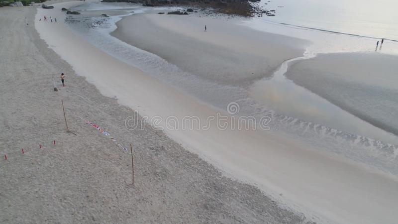 惊人的海滩的鸟瞰图与走在沙子的排球网和人的 射击 美丽的海滩顶视图  库存照片