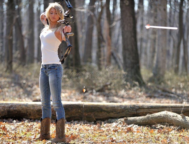 惊人的白肤金发的女性射手-离开弓的箭头 库存图片