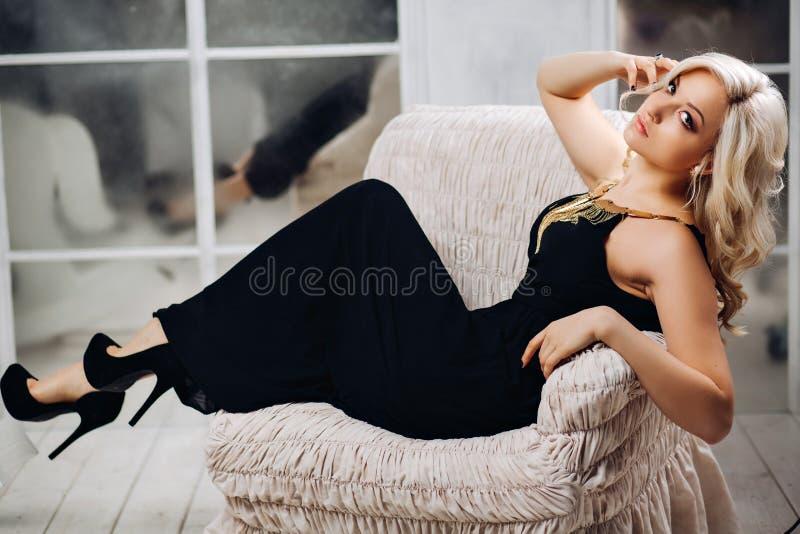 惊人的白肤金发的有别致的长的白肤金发的卷发的妇女美丽的性感的妇女在坐在豪华的一件典雅的黑礼服 图库摄影