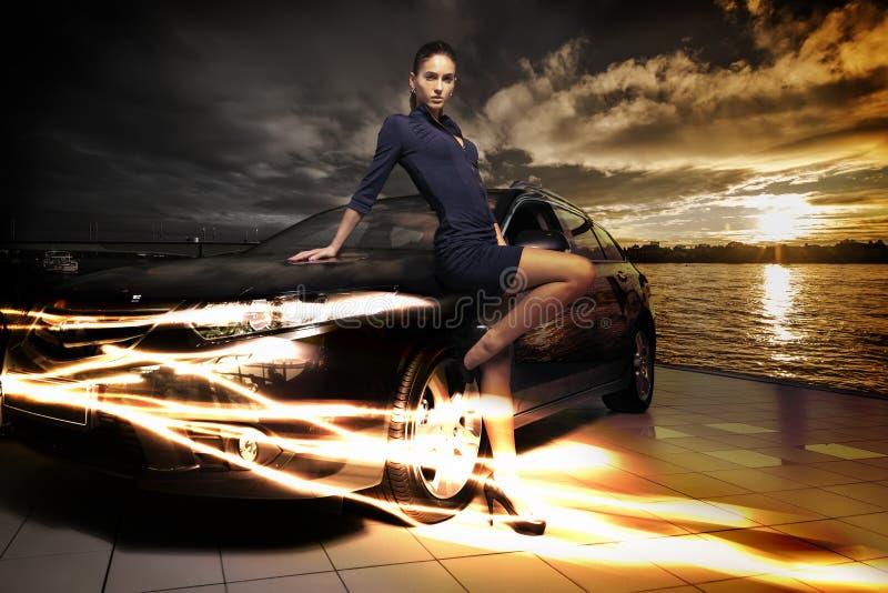 惊人的秀丽妇女摆在她的汽车旁边的,意想不到的风景背景 库存照片