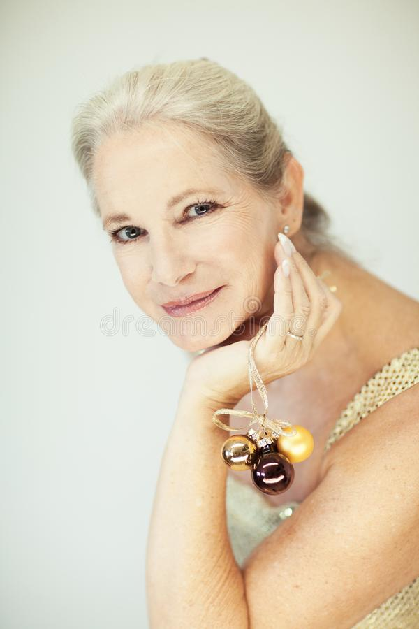 惊人的美好和自信最好变老了有灰色头发的妇女微笑入照相机的,拿着圣诞节装饰中看不中用的物品 免版税库存图片
