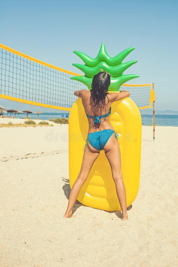 惊人的被晒黑的女孩的夏天图象黄色可膨胀的菠萝床垫的在排球场 免版税库存图片