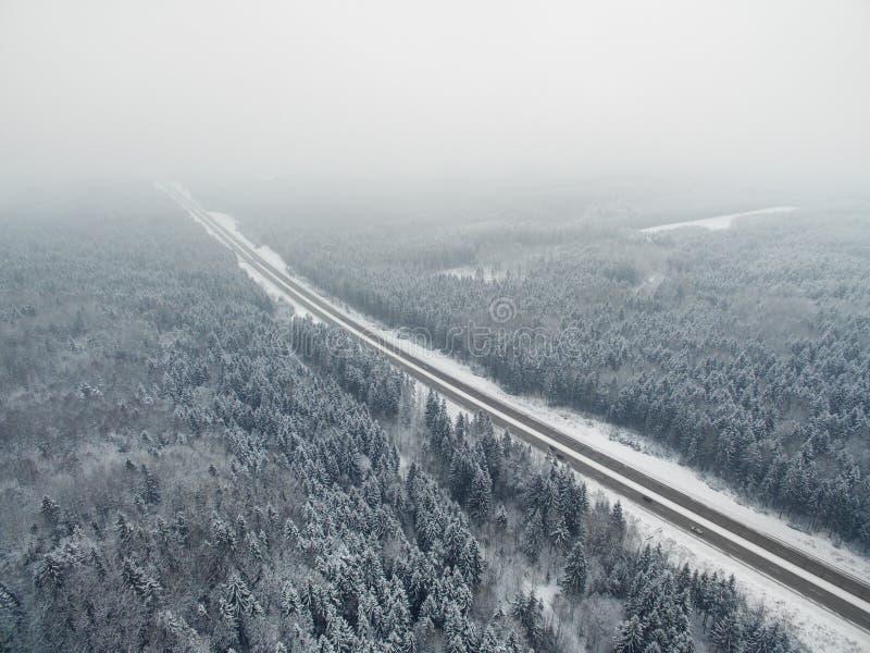 惊人的路在有驾驶的汽车冻冬天森林里 有雾的尽头透视 在北部的空中全景 库存图片