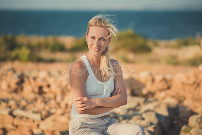 惊人的轻的白色时髦的衣裳性感摆在的夫人白肤金发的妇女在海边海滩空气 看对在ancie的照相机的闪烁发光物女孩 免版税图库摄影