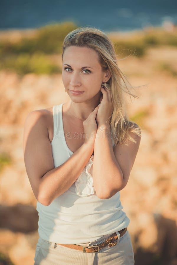 惊人的轻的白色时髦的衣裳性感摆在的夫人白肤金发的妇女在海边海滩空气 看对在ancie的照相机的闪烁发光物女孩 库存照片