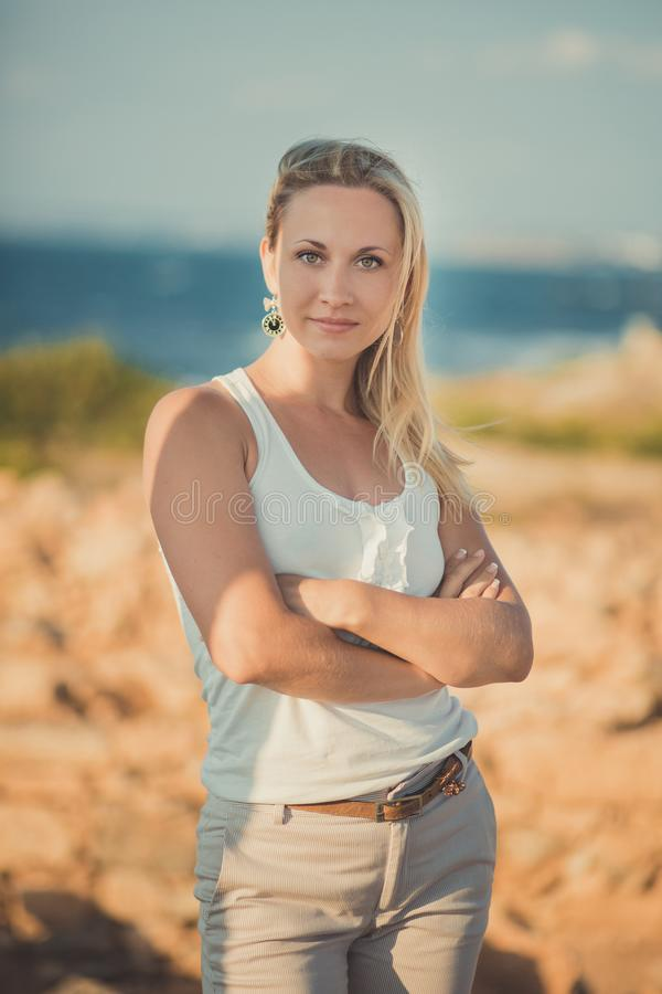 惊人的轻的白色时髦的衣裳性感摆在的夫人白肤金发的妇女在海边海滩空气 看对在ancie的照相机的闪烁发光物女孩 库存图片