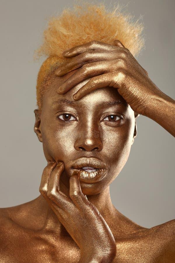 惊人的非洲人Amercian妇女绘与金子 库存照片