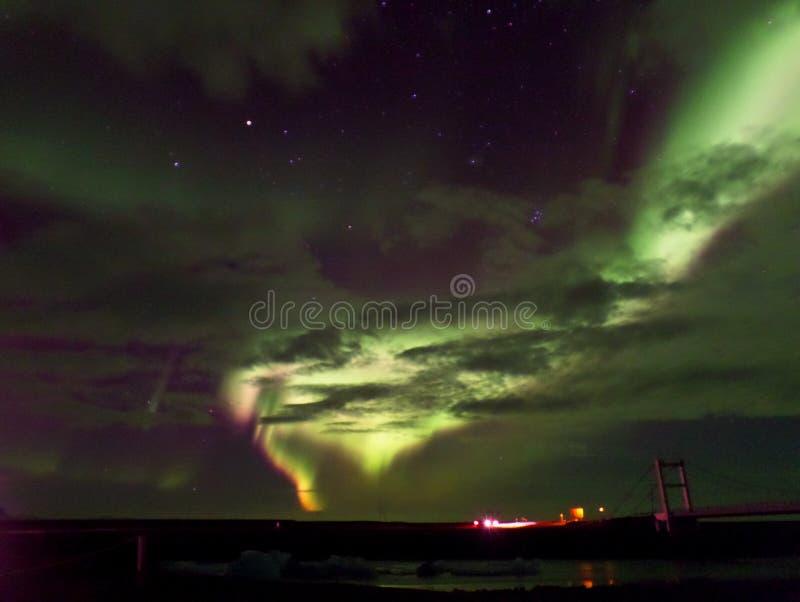 惊人的绿色和桃红色极光闪动在桥梁和冰川盐水湖的多云天空的Borealis 免版税库存照片