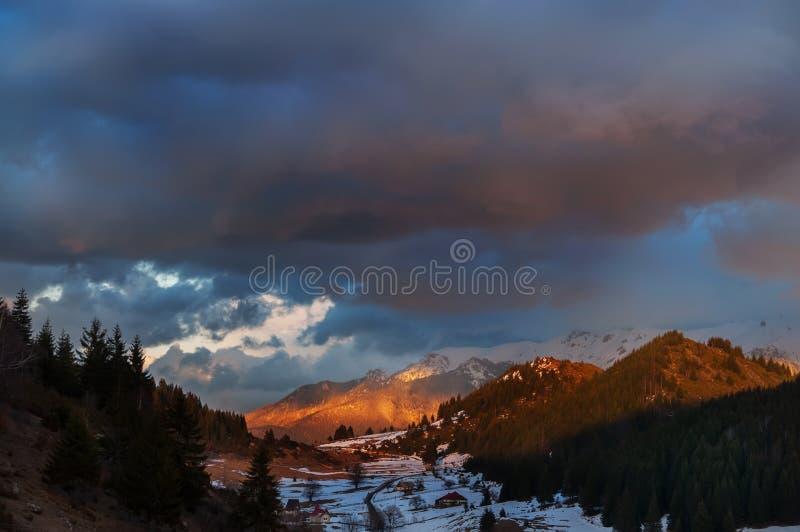 惊人美好的日落在山和小屋谷的在云杉的森林冬天,春天风景中 rom 免版税库存照片