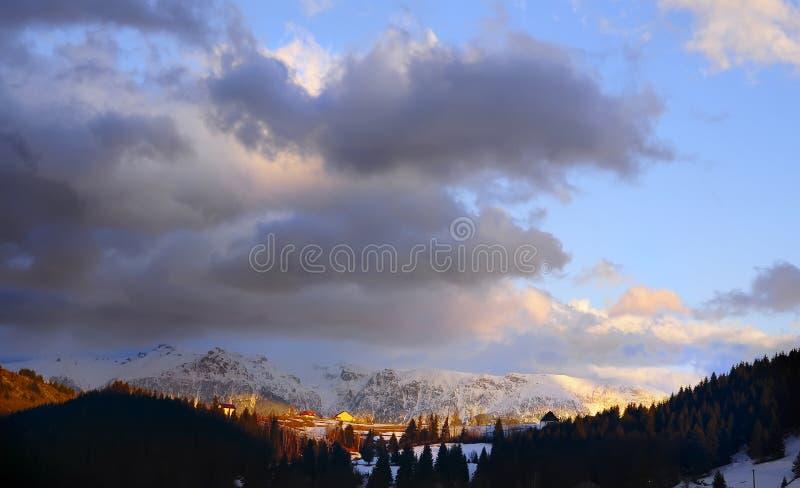 惊人美好的日落在山和小屋谷的在云杉的森林冬天,春天风景中 rom 图库摄影