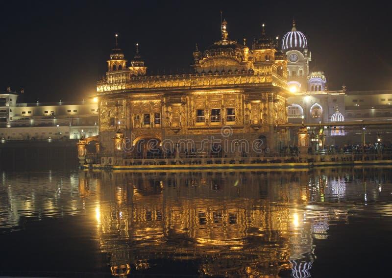 惊人金黄寺庙夜视图,光的反射 免版税库存照片