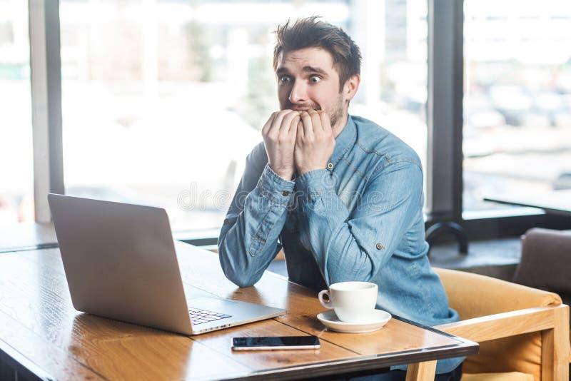 惊吓!情感紧张的年轻商人侧视图画象在蓝色牛仔裤衬衣的在咖啡馆、运作的onlone和钉子坐 免版税库存照片