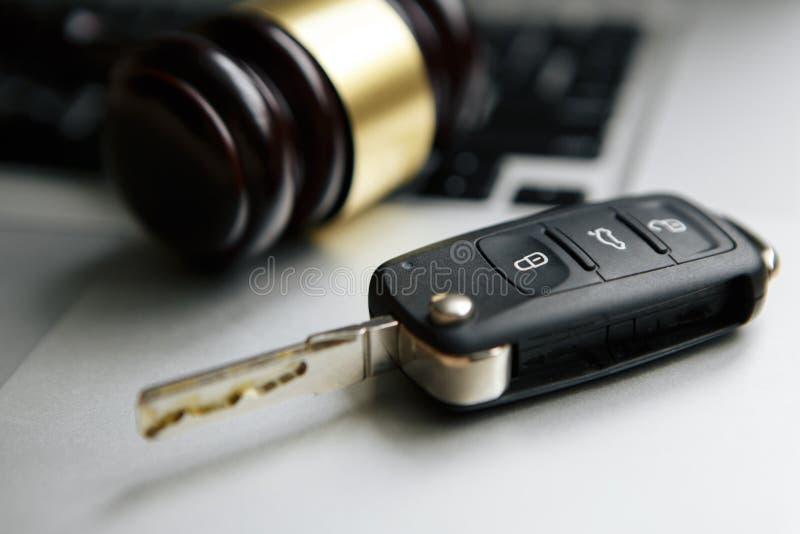 惊堂木和汽车钥匙特写镜头在听起来块的反对灰色背景 免版税图库摄影