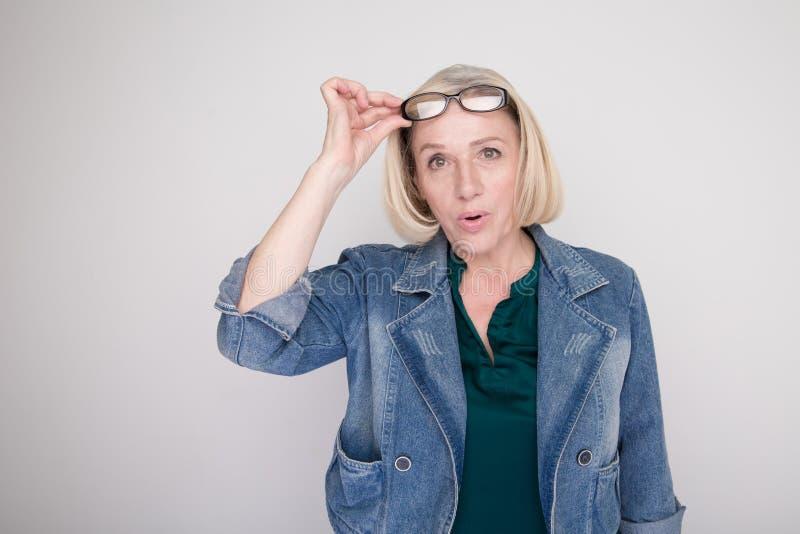 惊奇和退出的白肤金发的妇女张了她的嘴并且在一个白色演播室举起她的玻璃 库存图片