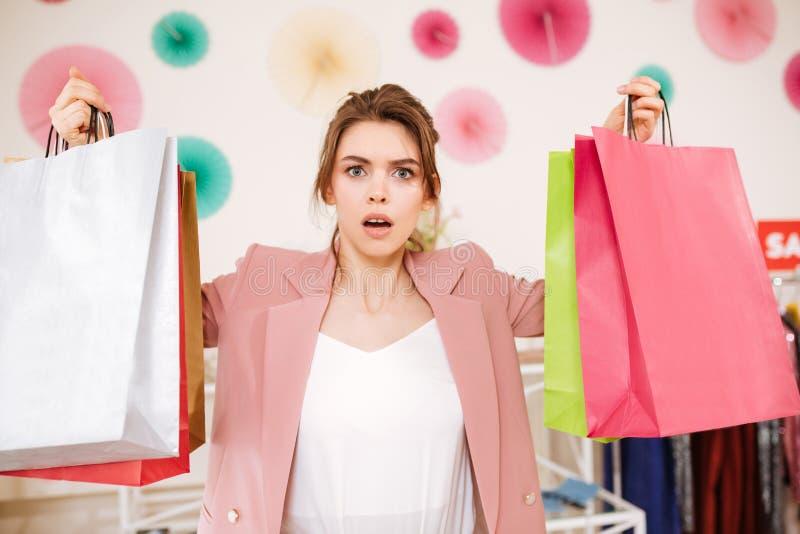 惊奇地看在与五颜六色的购物带来的照相机的少女在手上在衣裳商店 免版税库存照片