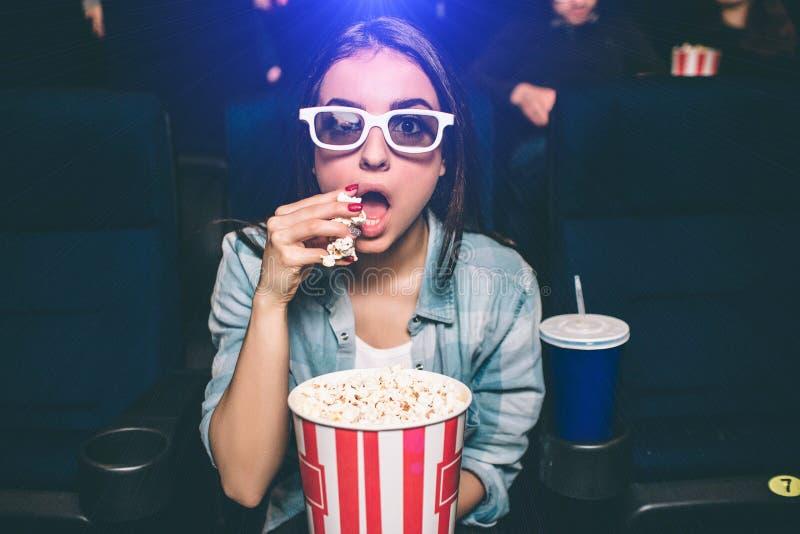 惊奇女孩坐非常紧密并且看得直接 她戴观看的电影的特别3d眼镜 女孩吃着 库存照片