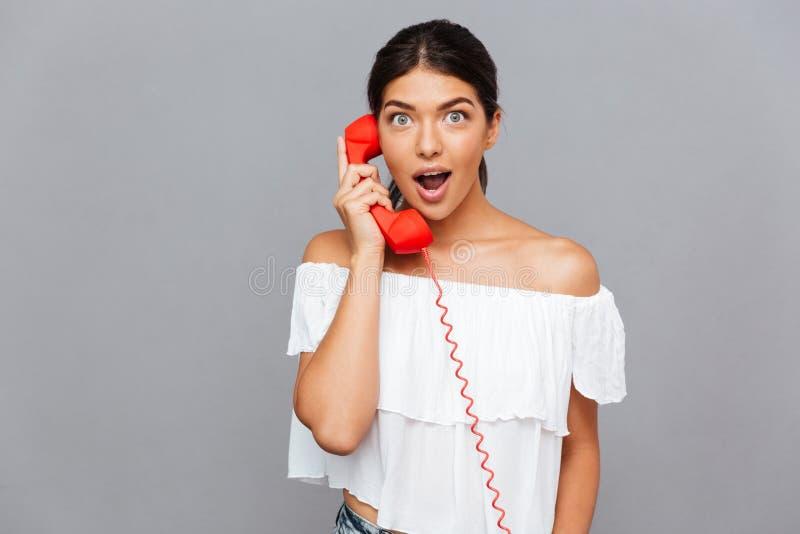 惊奇妇女谈话在电话管 免版税库存照片