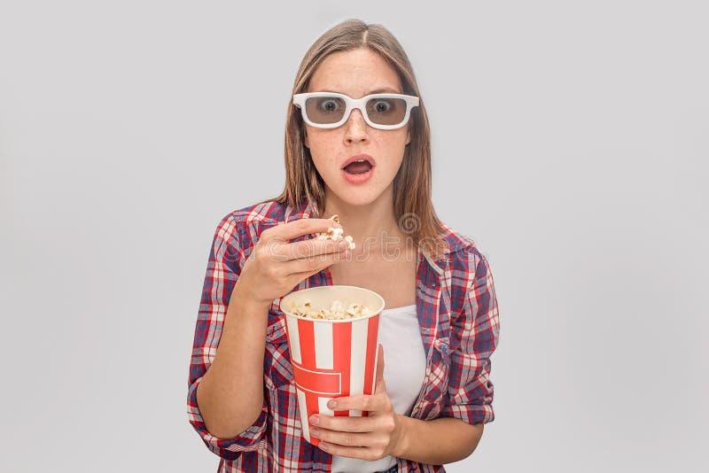 惊奇年轻女人保持嘴张和神色通过玻璃 她在一手和极少数上拿着箱玉米花它 库存照片