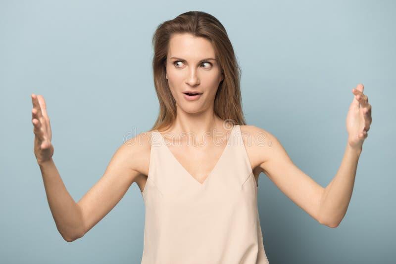 惊奇年轻女人展示大规模测量用手 免版税图库摄影